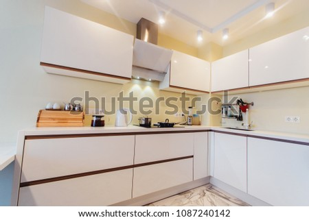 Modern kitchen white furniture with a table top made of natural stone. Advertising photography of kitchen interior. View of the kitchen from the front close #1087240142