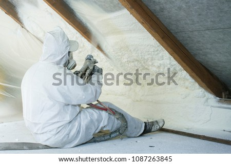 spray polyurethane foam for roof - technician spraying foam insulation using plural component gun for polyurethane foam, inside #1087263845