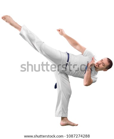 Man trains capoeira in studio isolated on white background. The man does the fighting element of capoeira. #1087274288