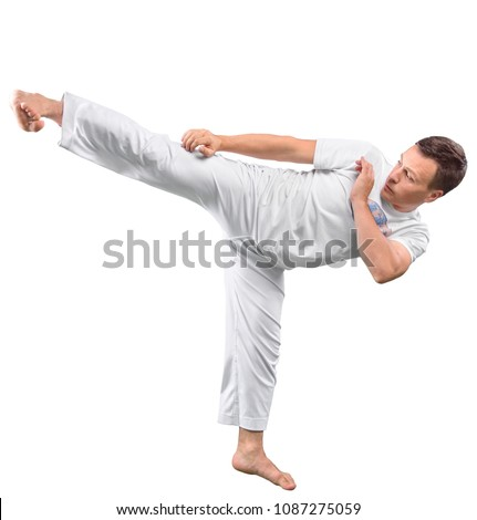 Man trains capoeira in studio isolated on white background. The man does the fighting element of capoeira. #1087275059