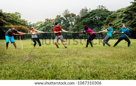 Team competing in tug of war #1087310306