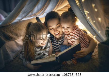 Family bedtime. Mom and children daughters are reading a book in tent. Pretty young mother and lovely girls having fun in children room. #1087354328