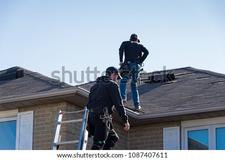 Two roofers inspecting a damaged roof #1087407611