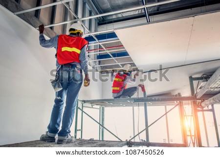 Construction worker wear safety uniform installation ceiling work #1087450526