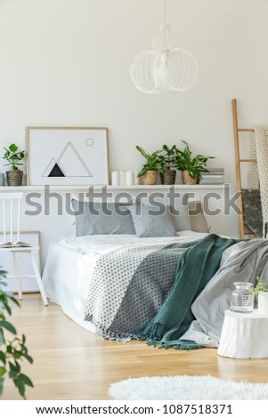 Bed, rug, shelf, chair and ornaments in bright bedroom interior #1087518371