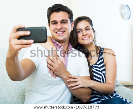 Cheerful young spouses posing and making selfie on smartphone. Focus on the man #1087618793