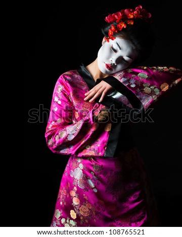 Portrait of geisha dancing isolated on black #108765521