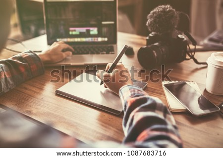 Youtuber editing video on laptop for up to worldwide through an online freelance work. Royalty-Free Stock Photo #1087683716