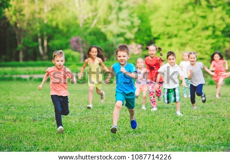 Many different kids, boys and girls running in the park on sunny summer day in casual clothes #1087714226