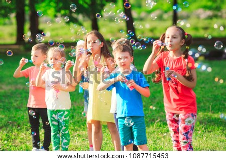 Group of children blowing soap bubbles #1087715453