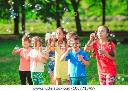 Group of children blowing soap bubbles #1087715459