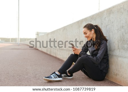 Photo of cheerful young asian sports woman sitting outdoors listening music using mobile phone.