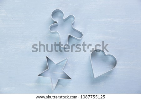 Three metal cookie cutters of different shapes with a star, heart and gingerbread man on a textured blue white background #1087755125