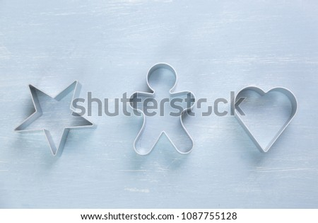 Three metal cookie cutters of different shapes with a star, heart and gingerbread man on a textured blue white background #1087755128