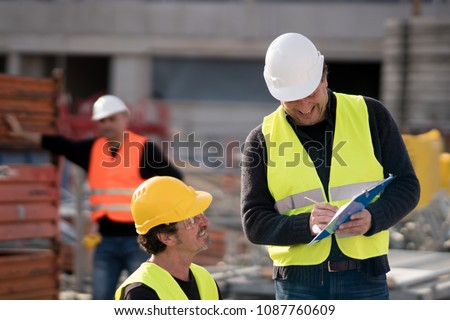 Civil engineer giving instructions to construction workers on construction site #1087760609