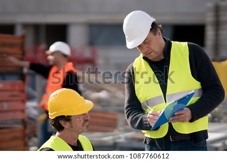 Civil engineer giving instructions to construction workers on construction site #1087760612