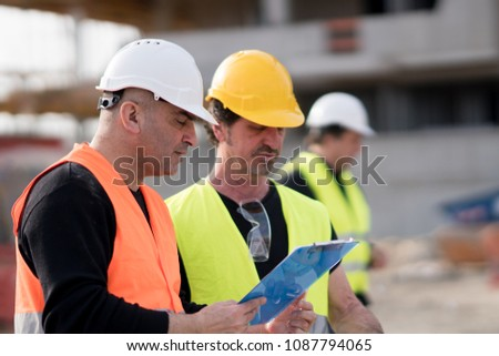 Civil engineers and construction workers at work on construction site #1087794065