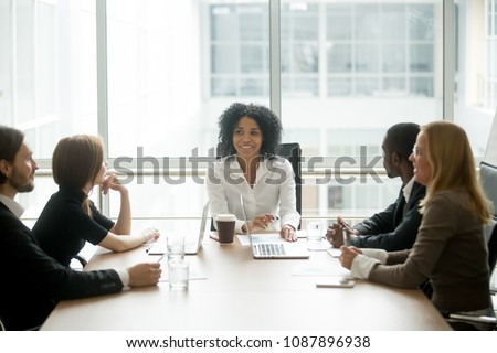 Smiling friendly african female boss leading corporate diverse team meeting talking to multiracial partners employees discussing results or planning work at group multi-ethnic briefing in boardroom #1087896938