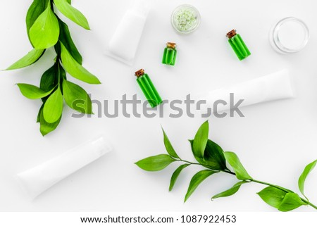 Organic skin care products. Cream, lotion, tonic. oil near green leaves on white background top view #1087922453