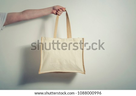 Mock-up cotton handmade eco shopping bag in hand #1088000996