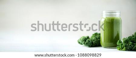Glass jar mugs with green health smoothie, kale leaves, lime, apple, kiwi, grapes, banana, avocado, lettuce. Copy space, sunlight effect. Raw, vegan, vegetarian, detox, alkaline food concept. #1088098829