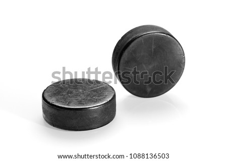 Two hockey pucks on a white background. Texture, background, concept #1088136503