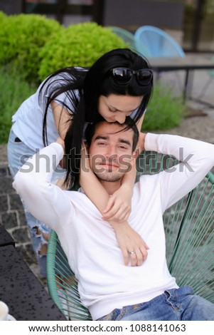 Wife kissing husband sitting in chair at street cafe outside. Concept of relationship and emotions. #1088141063