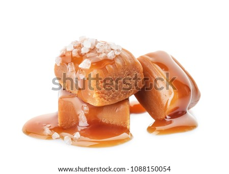 Delicious candies with caramel sauce and salt on white background Royalty-Free Stock Photo #1088150054