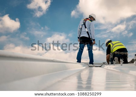 Construction engineer wear safety uniform inspection metal roofing work for roof industrial concept with copy space #1088250299