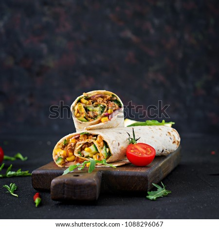 Burritos wraps with beef and vegetables on  black background. Beef burrito, mexican food. #1088296067