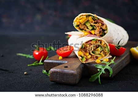 Burritos wraps with beef and vegetables on  black background. Beef burrito, mexican food. #1088296088