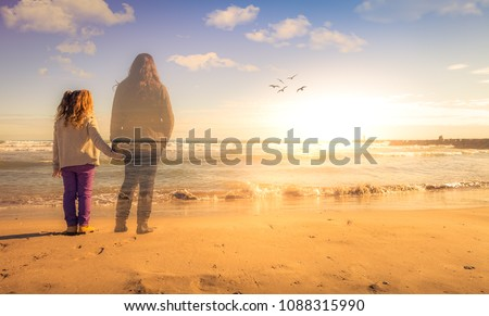 Absence. A girl holds the hand of the spirit of her deceased mother. The two are watching the sunset. Royalty-Free Stock Photo #1088315990