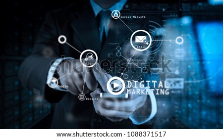Digital marketing media (website ad, email, social network, SEO, video, mobile app) in virtual screen.Businessman hand using mobile phone with digital layer effect as business strategy.              #1088371517