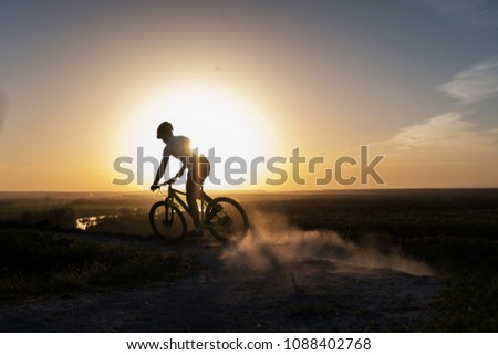 Cyclist riding mountain bike on trail at evening. Healthy life style and outdoor adventure. #1088402768