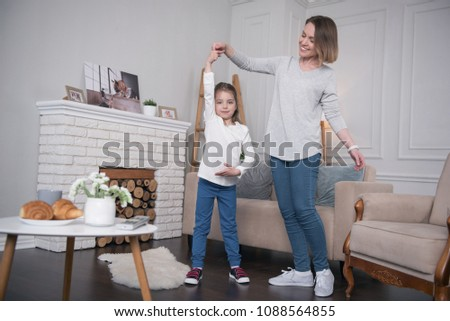 I love dancing. Content little girl smiling and dancing with her mother at home #1088564855