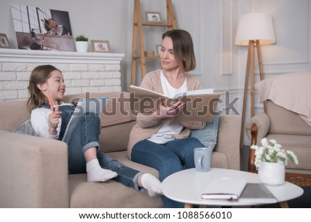 Wonderful day. Adorable glad girl sitting on the couch with her mother and studying #1088566010
