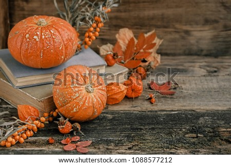 autumn cozy still life. pumpkins, autumn leaves and books on wooden background. fall season, thanksgiving holiday, Halloween concept. autumn atmosphere composition. #1088577212