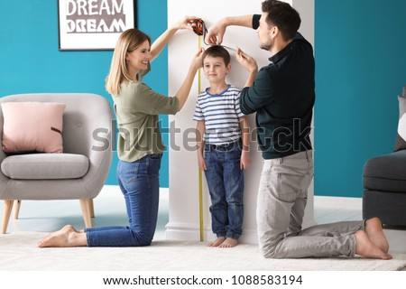 Parents measuring height of their son at home #1088583194