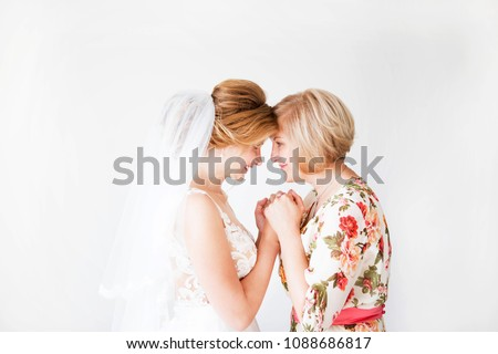 Wedding morning of the bride. Mother of the bride blesses the bride for a happy family life. Mom and her daughter joined hands. In the background a bright wall. #1088686817