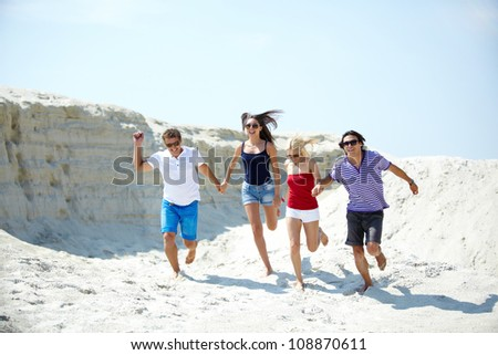 Ecstatic young people running on the sand holding hands #108870611
