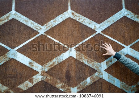 background of rusted vintage metal with a diamond pattern and vintage blue paint and a slender open female hand #1088746091