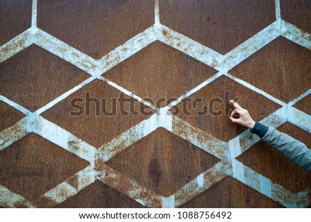 background of rusted vintage metal with a diamond pattern and vintage blue paint and a slender female hand signing ok #1088756492