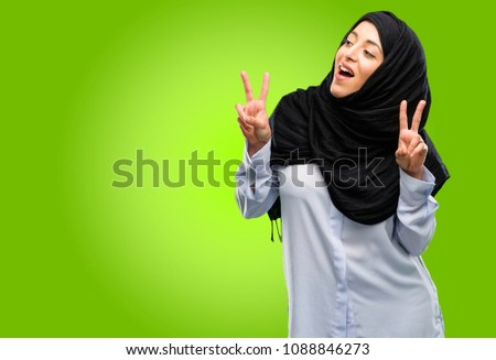 Young arab woman wearing hijab happy and excited expressing winning gesture. Successful and celebrating victory, triumphant #1088846273