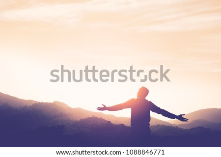 Copy space of man rise hand up on top of mountain and sunset sky abstract background. Freedom and travel adventure concept. Vintage tone filter effect color style. Royalty-Free Stock Photo #1088846771
