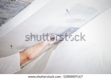 manual worker with wall plastering tools worker putty wall and ceiling #1088889167