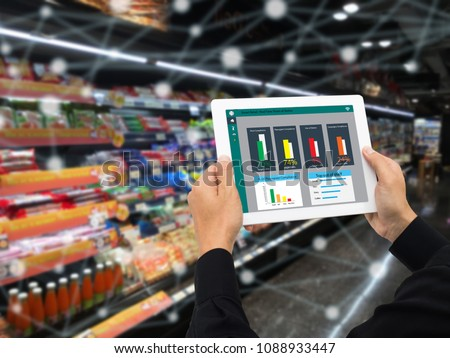 iot smart retail in the futuristic concept, the retailer hold the tablet and use augmented reality technology monitor data of out of shelve, price, planogram, campaign of compliance in the real time #1088933447