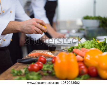 Chef hands preparing marinated Salmon fish fillet for frying in a restaurant kitchen #1089043502