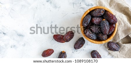 Bowl of dates and a linen cloth on a white concrete background. The view from the top. Royalty-Free Stock Photo #1089108170