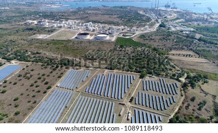 Aerial picture of solar park and oil depot in background the solar park is photovoltaic system designed for supply of merchant power into the electricity grid producing sustainable renewable energy