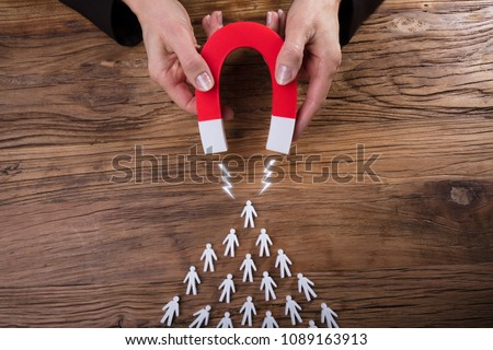 Businessperson's Hand Attracting Human Figures With Horseshoe Magnet On Wooden Desk Royalty-Free Stock Photo #1089163913